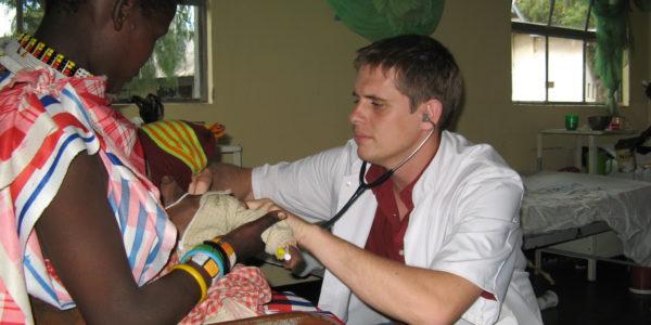 Photo 2: Christian examines a child