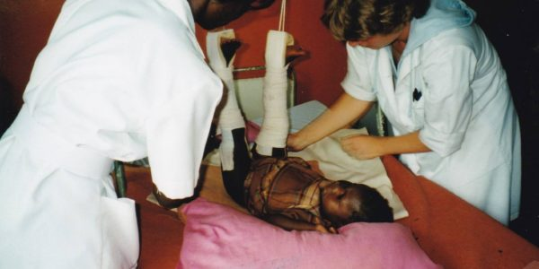 Then: Ward round; a baby girl in Gallows traction for a fractured femur